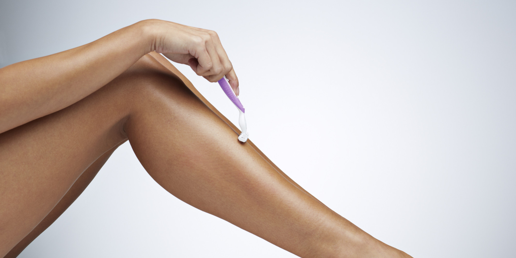 Close-up of woman shaving her leg
